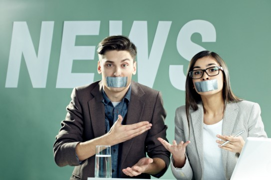 News presenters with taped mouths on TV